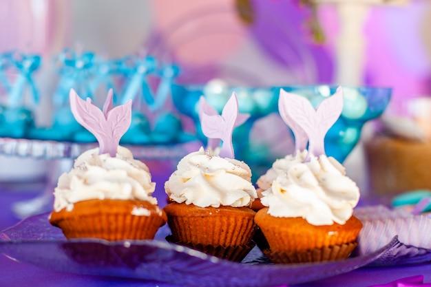 白いトッピングでカップケーキを持つ子供のためのテーブルには、紫色の人魚の尾が飾られています。