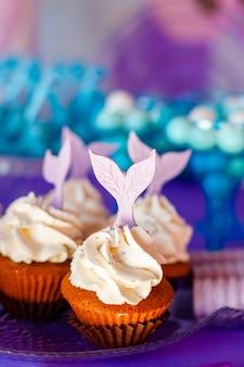 День рождения концепция для девочки. стол для детей с кексами с декорированным топиндами фиолетовым хвостом русалки. летний сезон вкусно на вечеринке