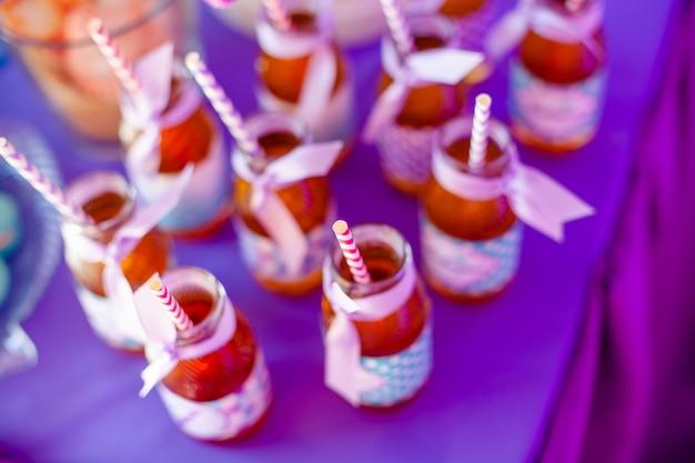 リンゴジュースのボトル、その上の特別なラベル、白とピンクのストロー