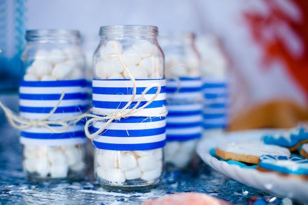 Стол с морским декором и тарелкой со сладостями, конфетами, печеньем и украшением баночек с зефиром