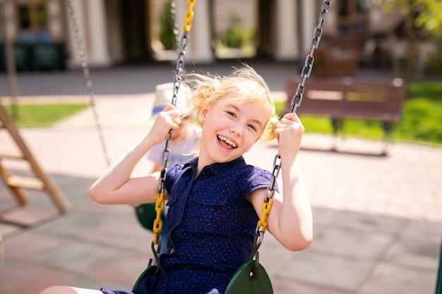 Мальчик в очках и шляпе и блондинка в платье, развлекаясь на качелях вместе в красивом летнем саду.