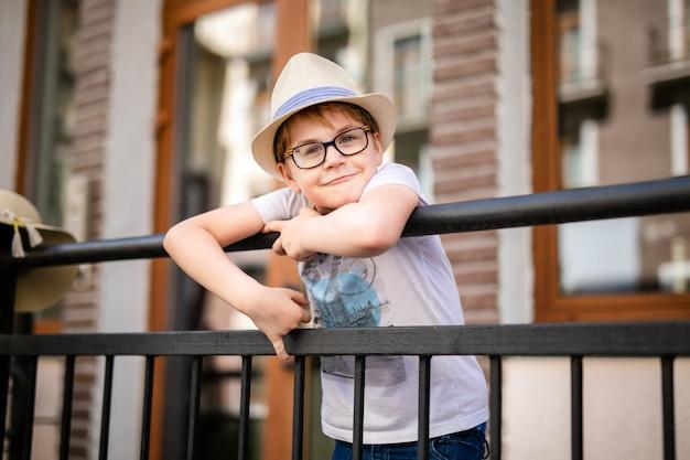麦わら帽子と美しい古い家の中で滞在する大きなメガネの金髪の少年