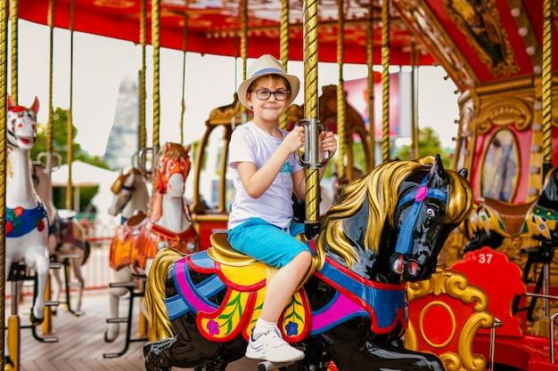 Белокурый мальчик в соломенной шляпе и большие очки верхом на разноцветной лошади в карусели карусели.