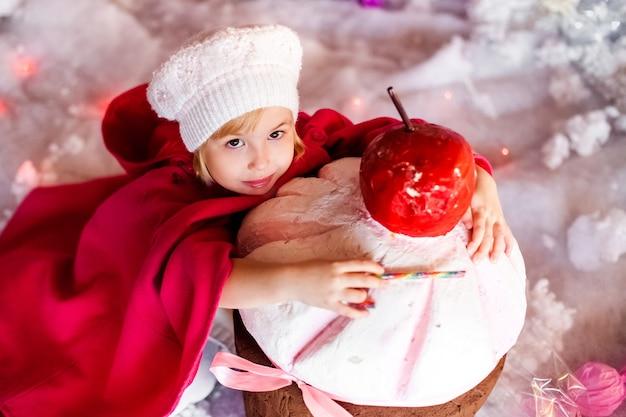 白いベレー帽、赤いブーツ、ピンクのマントと巨大な人工ケーキを持つ金髪の微笑の女の子の肖像画