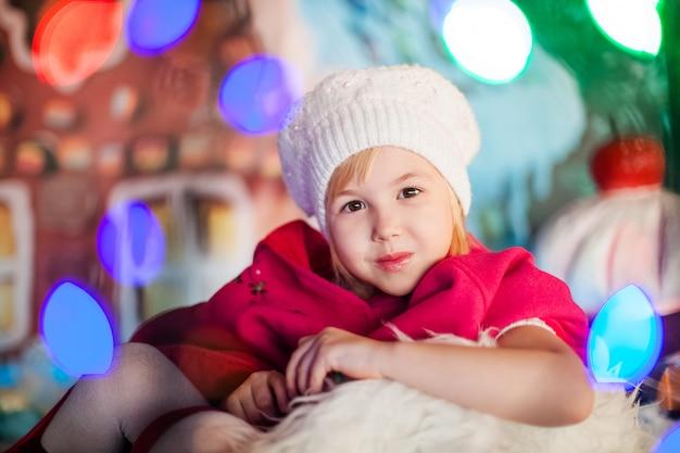 白いベレー帽、赤いブーツ、ピンクのマントと小さな金髪の微笑の女の子の肖像画