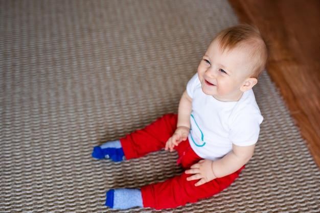 Маленький мальчик в белой футболке с игрушками на полу у себя дома