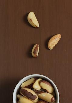 木製のテーブルの上にボウルにブラジルナッツ