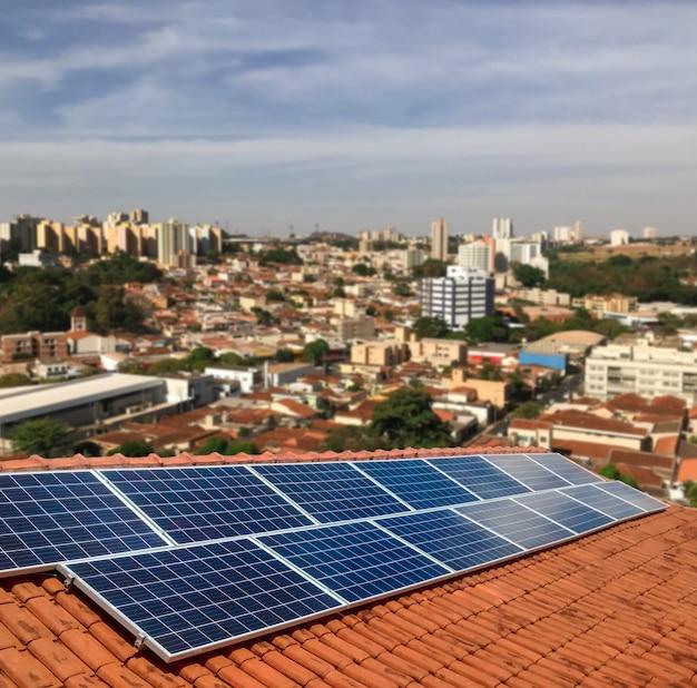 晴れた日に住宅の屋根の上の太陽光発電 - 持続可能な資源の太陽エネルギーの概念