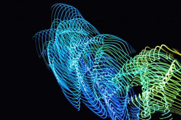 抽象ネオンライトは黒い背景で追います。未来オーバーレイ光パターン。