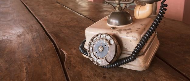 ヴィンテージ-木製のテーブルにレトロな古いベージュ電話