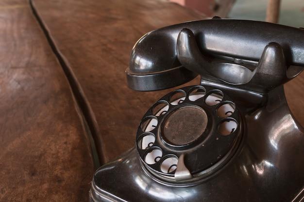 ヴィンテージ-木製のテーブルにレトロな古い黒電話