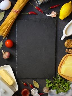 パスタ、スパゲッティまたはブカティーニとトマトソースの材料。食品の背景。コピースペース