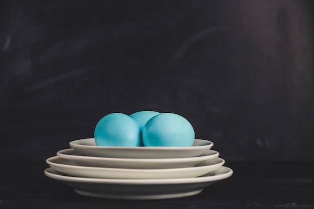 Синие пасхальные яйца на тарелках