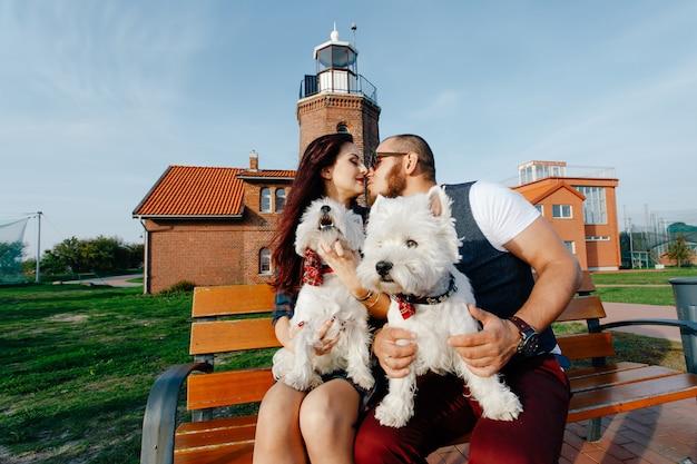 Муж целует жену, сидя на скамейке, и на коленях у них два маленьких щенка