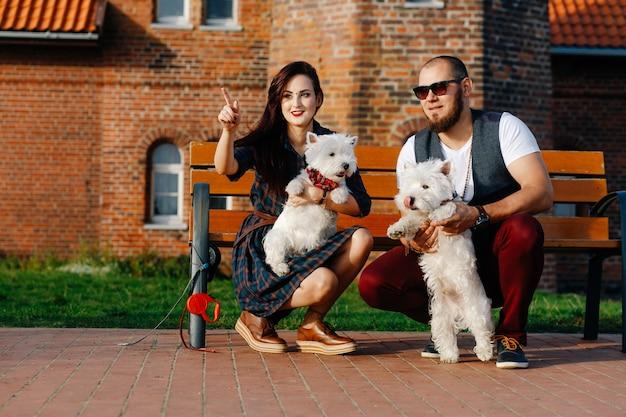 愛情のあるカップルは屋外で彼らの白いかわいい子犬と一緒に楽しい時間を過ごします