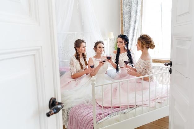 花嫁はベッドの上にピンクのドレスでブライドメイドと一緒に座っているし、ワインを飲みます。