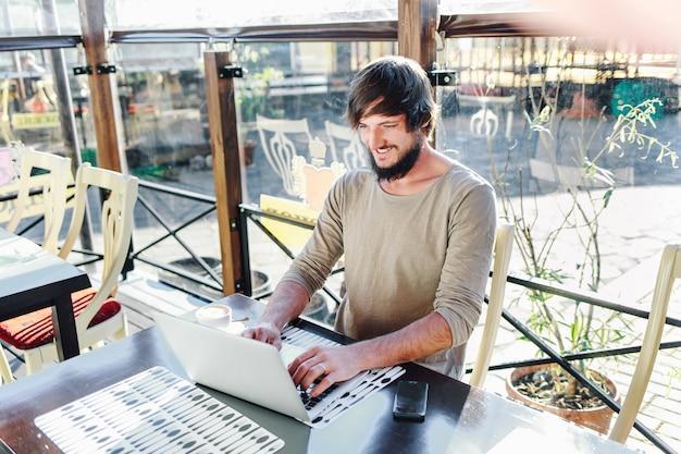 屋外カフェでノートパソコンを扱う若い魅力的な男