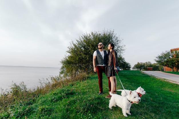 公園で白い犬を歩いている美しい妻と夫