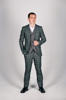 グレーの市松模様のスーツのスタイリッシュな男