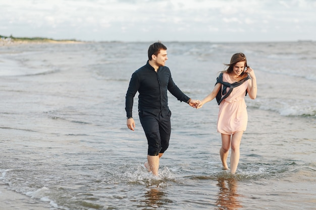 最初のデートの夕方、ビーチで海の波の上を走る愛情のあるカップル