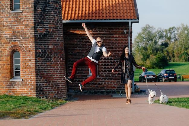 愛情のあるカップルは、屋外で白いかわいい子犬と一緒に楽しい時間を過ごします