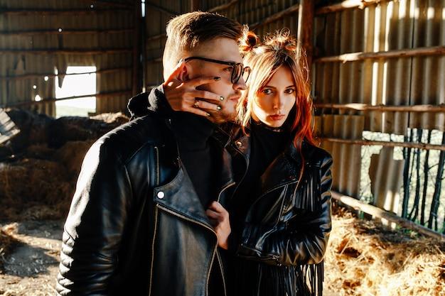 日没で赤い髪の少女とハグの男。革のジャケットに身を包んだ愛情のあるカップル