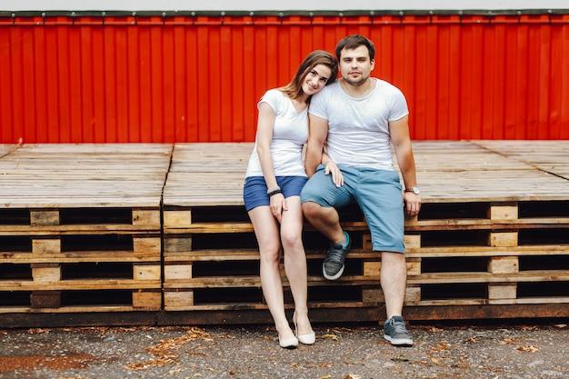 Влюбленная пара сидит на поддонах на фоне красной сцены летом