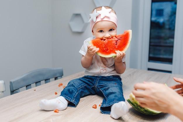 かわいい女の赤ちゃん、キッチンでスイカを食べる