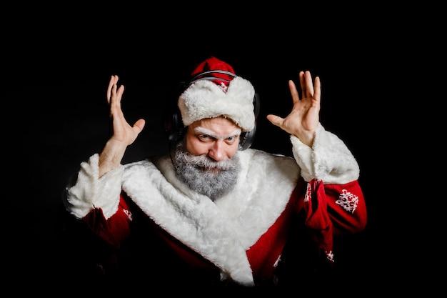 Санта-клаус слушает музыку в наушниках на черном фоне