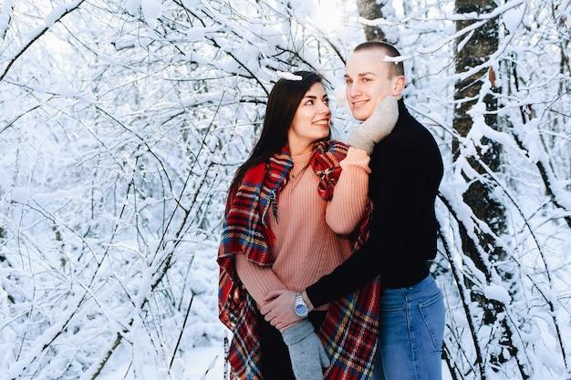 冬の森でカップルが笑う
