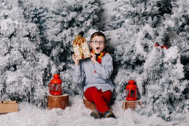少年は赤いズボンの切り株に座って、クリスマスプレゼントを開催