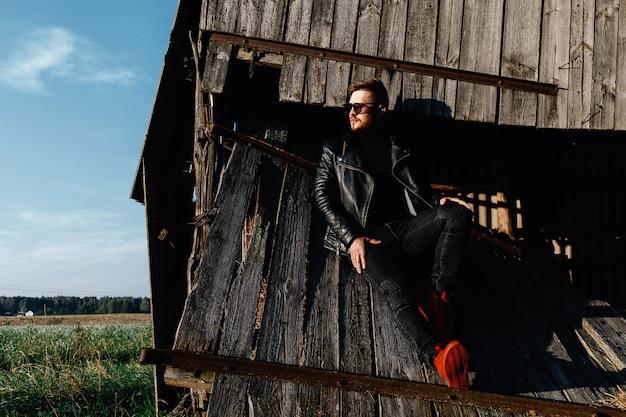 Бородатый парень в кожаной куртке и красных кроссовках сидит на фоне заброшенного здания