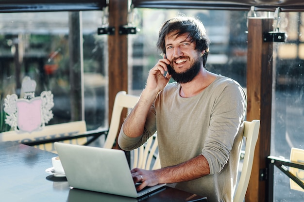 Человек / студент с помощью компьютера в кафе и разговаривает по телефону