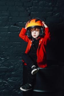 Мальчик в шлеме под люстрой в тускло освещенной комнате
