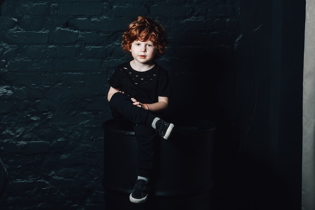 足を組んで座っている暗いカジュアルな服装でかわいい巻き毛の若い男の子の肖像画