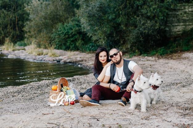 公園で彼らの白い犬を歩いて美しい妻と夫
