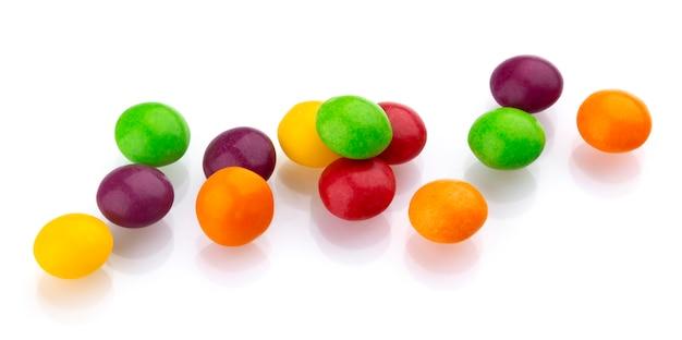 白い背景に分離された多色の光沢のあるナッツとレーズンの糖衣錠