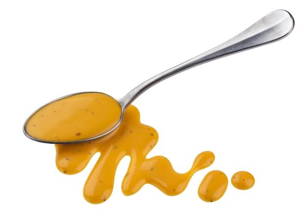 マスタードソース、白い背景に、上面に分離されたスプーンで蜂蜜サラダドレッシング