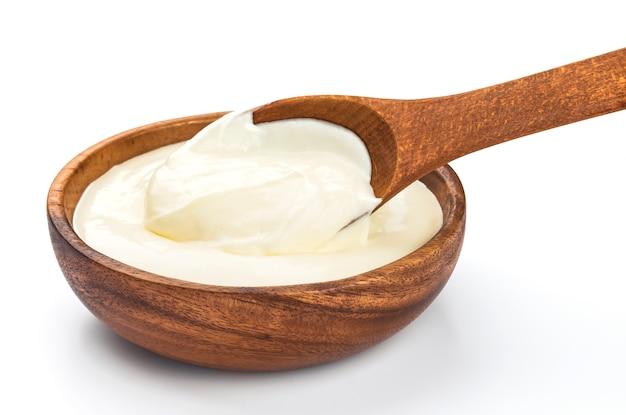 白で隔離される木製のボウルにサワークリーム