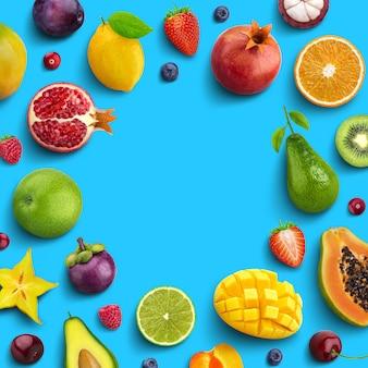 様々な果物や果実の青い背景、上面図、創造的なフラットレイアウト、テキスト用の空きスペースを持つ果物の丸いフレームに分離