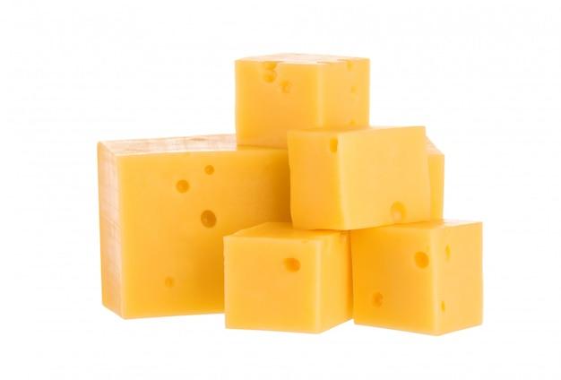 白で隔離されるチーズキューブのヒープ