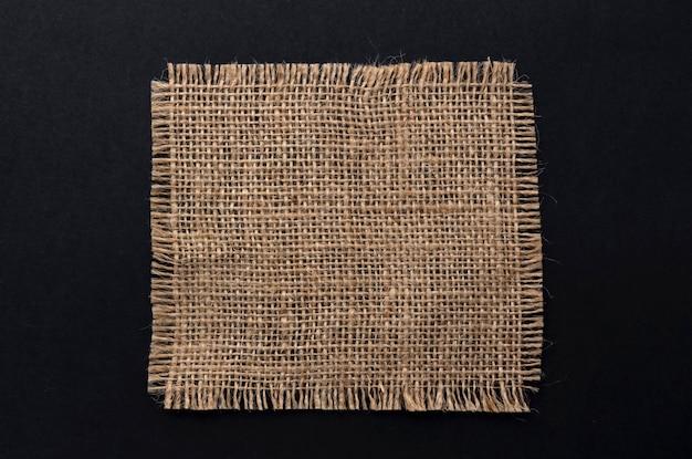 Старая салфетка из ткани мешковины на черном фоне, вид сверху