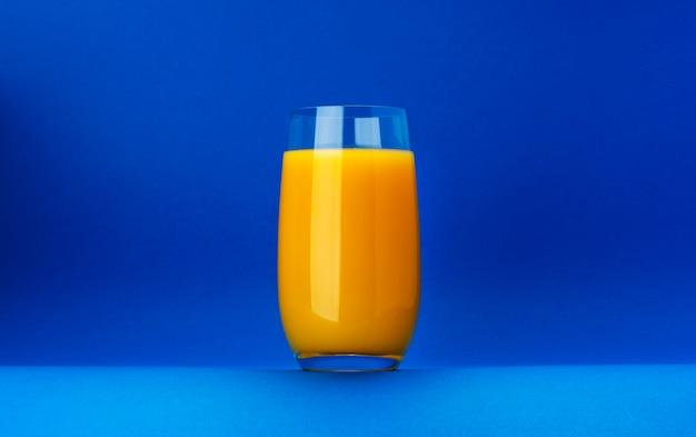 コピースペースと青色の背景に分離されたオレンジジュースのガラス
