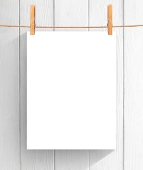 木製の背景上物干し用ロープにぶら下がっている紙の空のシート。コピースペースであなたのプロジェクトのためにモックアップ