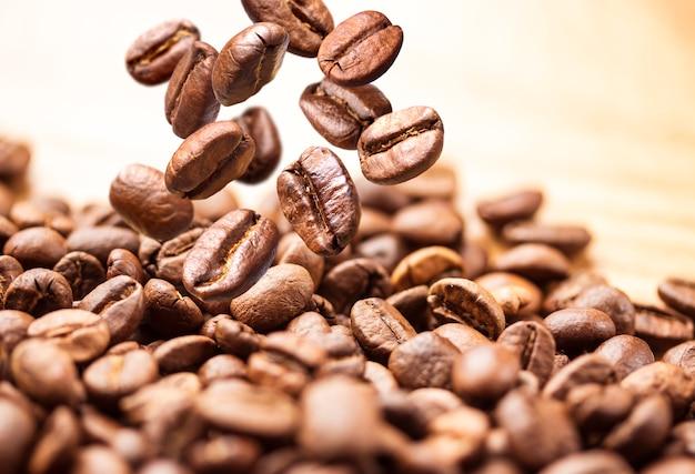 飛んでいるコーヒー豆。白い背景で隔離の山の上に落ちるコーヒー豆