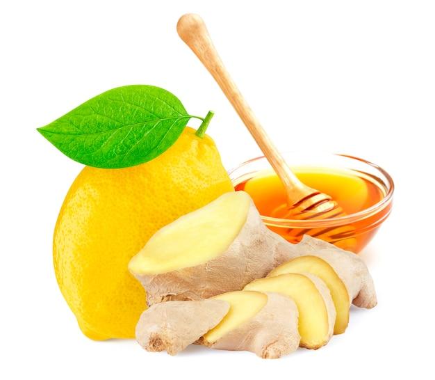 白で隔離される蜂蜜とショウガの根とレモン