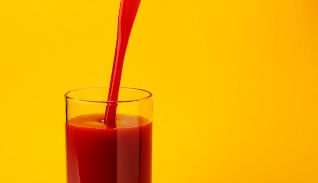 Томатный сок наливание в стакан, изолированные на желтый