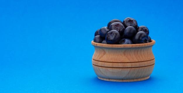 Черника в деревянной миске на синем фоне