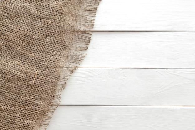 白い木製の背景に黄麻布の質感