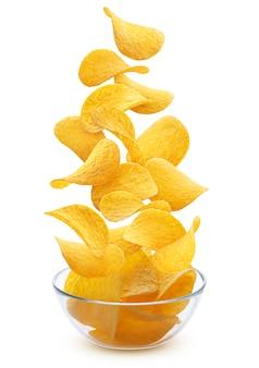 Куча вкусных хрустящих картофельных чипсов в стеклянной миске